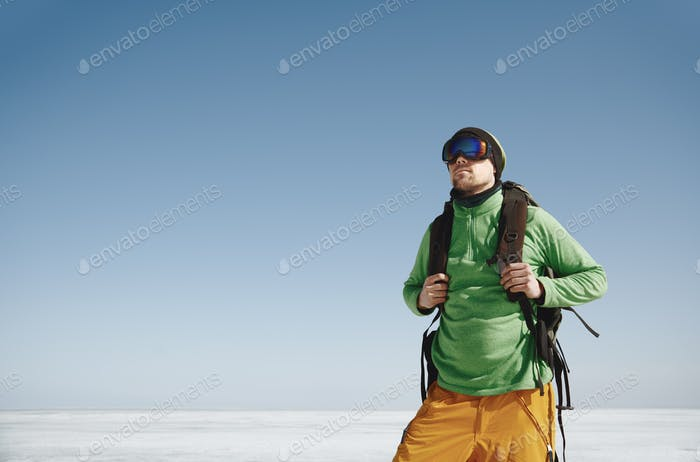 Young adult man with backpack outdoors exploring icy landscape