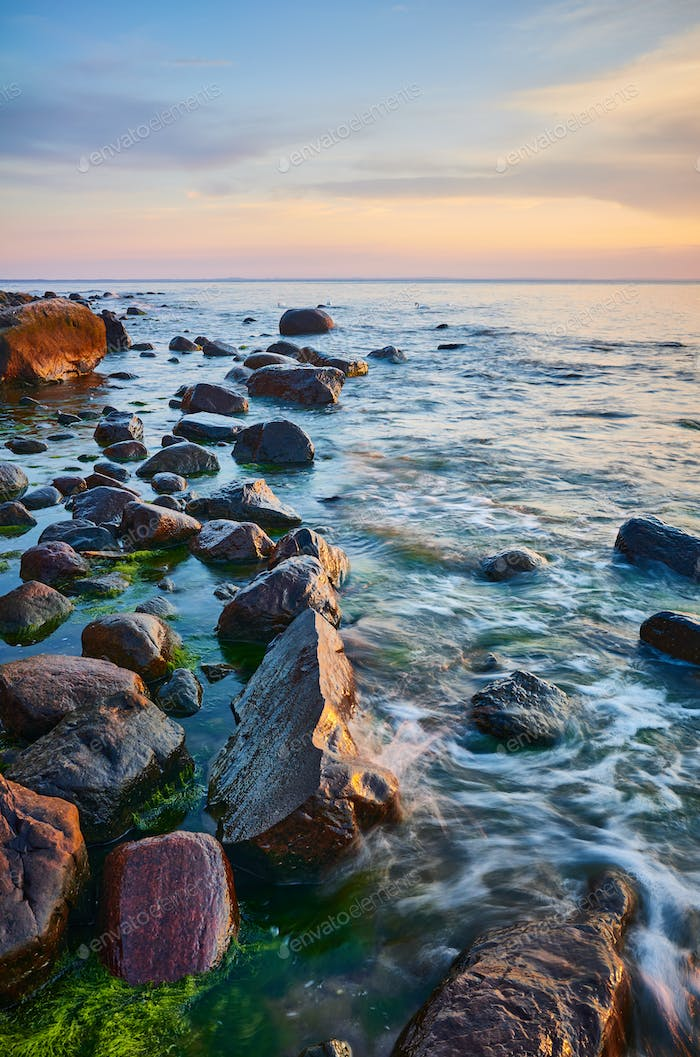 Baltic Sea coast with rocks in water at sunset.