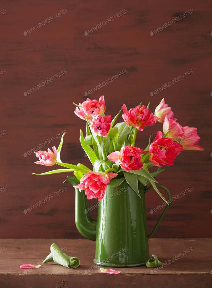 beautiful pink tulip flowers bouquet in green teapot