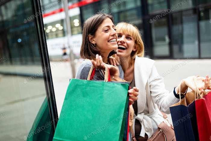 Beautiful women with shopping bags walking on street at the mall