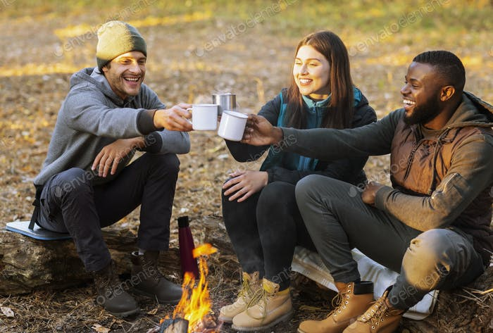 Веселые туристы тосты за приятный кемпинг в закате огней