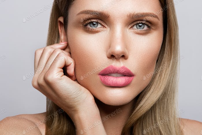 Beautiful young model with pink lips. Nude manicure