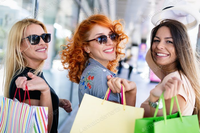 Grupo de Amigos Alegre sonriendo de compras en la Ciudad
