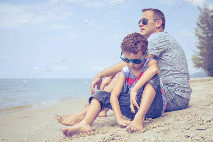 Portrait of young sad little boy and father sitting outdoors at