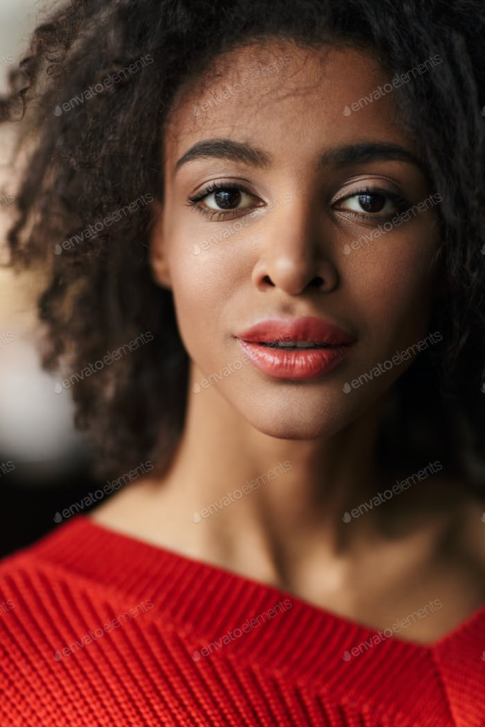 Beautiful young african woman wearing sweater standing over blurred background, looking at camera
