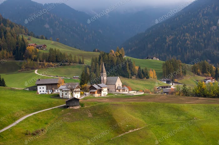 Green alpine valley with view of Santa Maddalena village church,