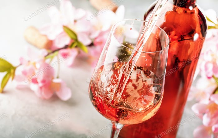 Rose wine pouring out of the bottle, gray background, pink flowers