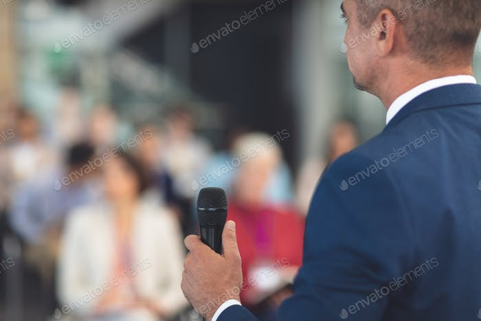 Rear view of mixed race businessman speaking at a business seminar in modern office