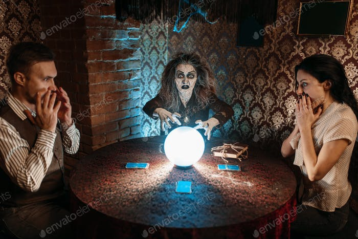 Witch reads scary spell over a crystal ball
