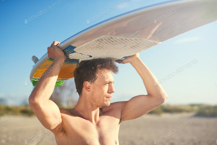 Handsome strong surfer carrying his surfboard