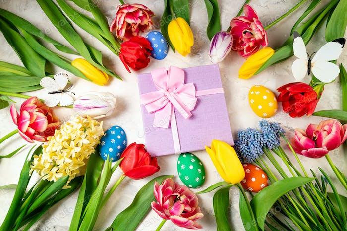 Frühlingshintergrund mit Blumen, Ostereiern und Geschenkbox Tulpen Frühlingsblumen