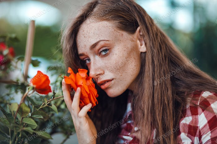 Beautiful freckled woman in checkered shirt smelling flower of rose, gardening concept