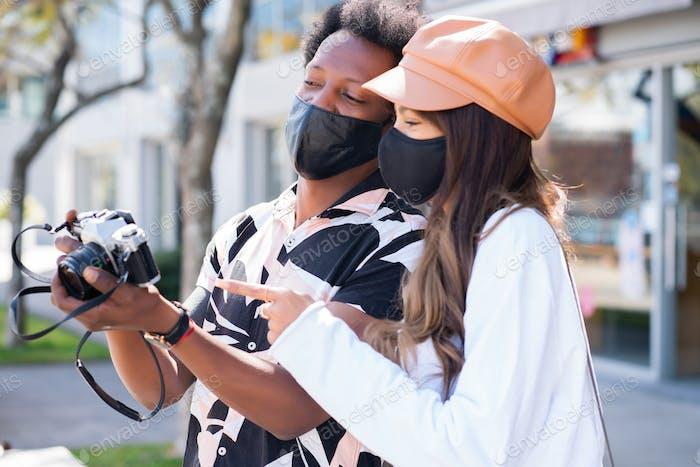 Tourist couple using camera outdoors.