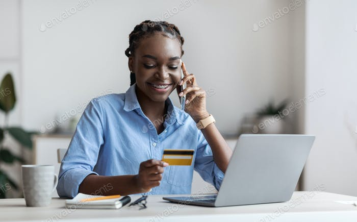 Smiling black female freelancer ordering online with credit card and cellphone