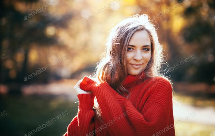 Natural young woman in soft warm knitted sweater walking outdoors, autumn and spring