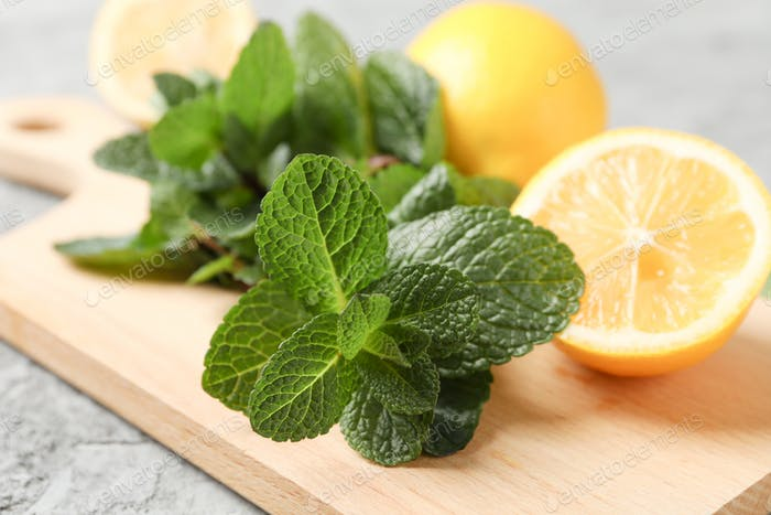 Cutting board with lemon and mint on grey background, close up