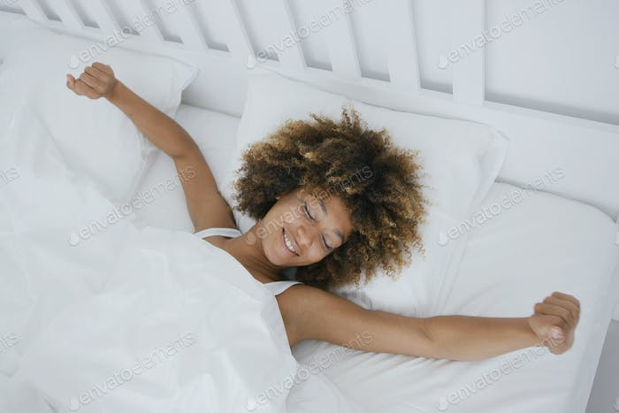 Content woman awakening in bed