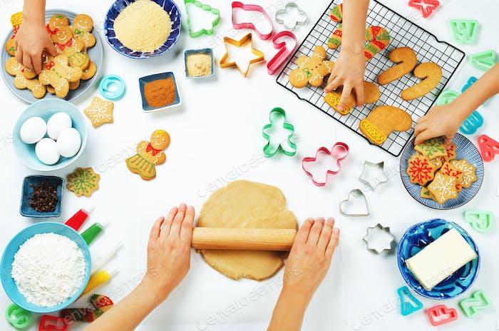 Frauenhände rollen Ingwerteig mit Kinderhänden, Lebkuchenkekse und Zutaten zum Backen