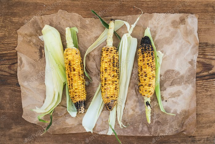 Grilled corn over oily craft paper and rustic wooden background, top view.