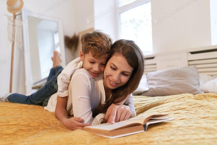 Lächelnde Mutter und Sohn umarmen und lesen gemeinsam Buch
