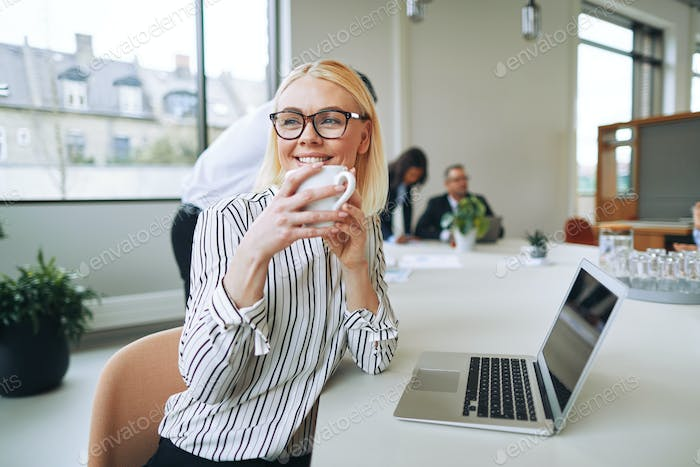 Smiling businesswoman enjoying a coffee while woring in an office