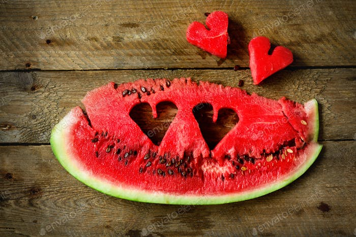 Piece of watermelon with heart shape on old wooden background. Copy space. Flat lay. Greeting card