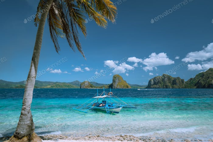 El Nido, Palawan, Philippines. Lonely filippino banca boat moored in turquoise ocean water. Island