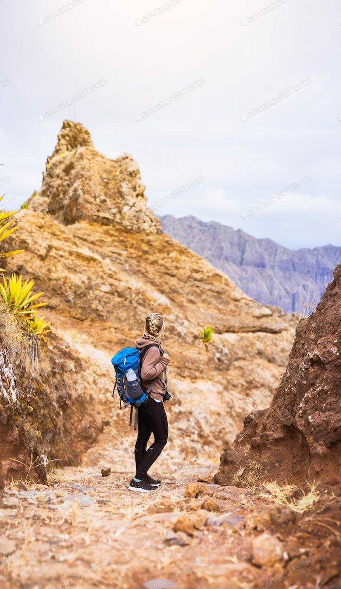 Wanderer auf dem steinigen Trekkingweg vor dem kargen Berggipfel auf der Insel Santo Antao