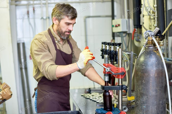 Bearded Worker Using Bottle Capper