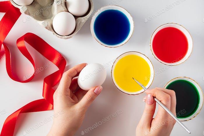 Junge Frau malt weiße Eier für Ostern.