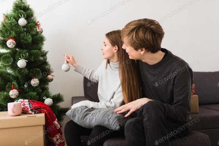 Portrait of beautiful young couple sitting on sofa at home and decorating Christmas tree together