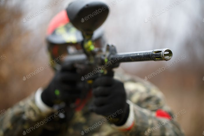 Paintball sport player wearing protective mask and aiming gun