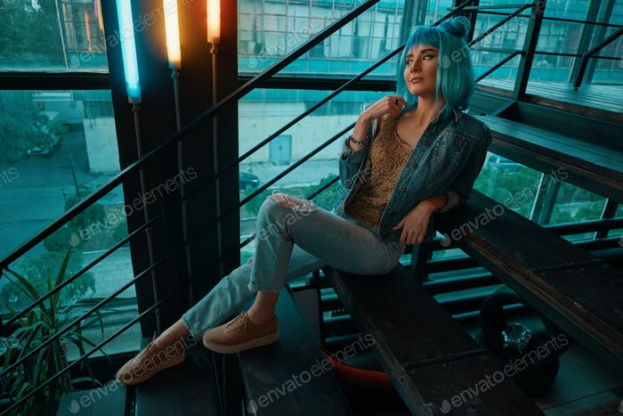 Stylish woman wearing a blue wig sitting on stairs in a modern
