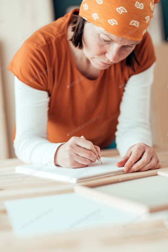 Female carpenter sketching project draft notes in woodwork works