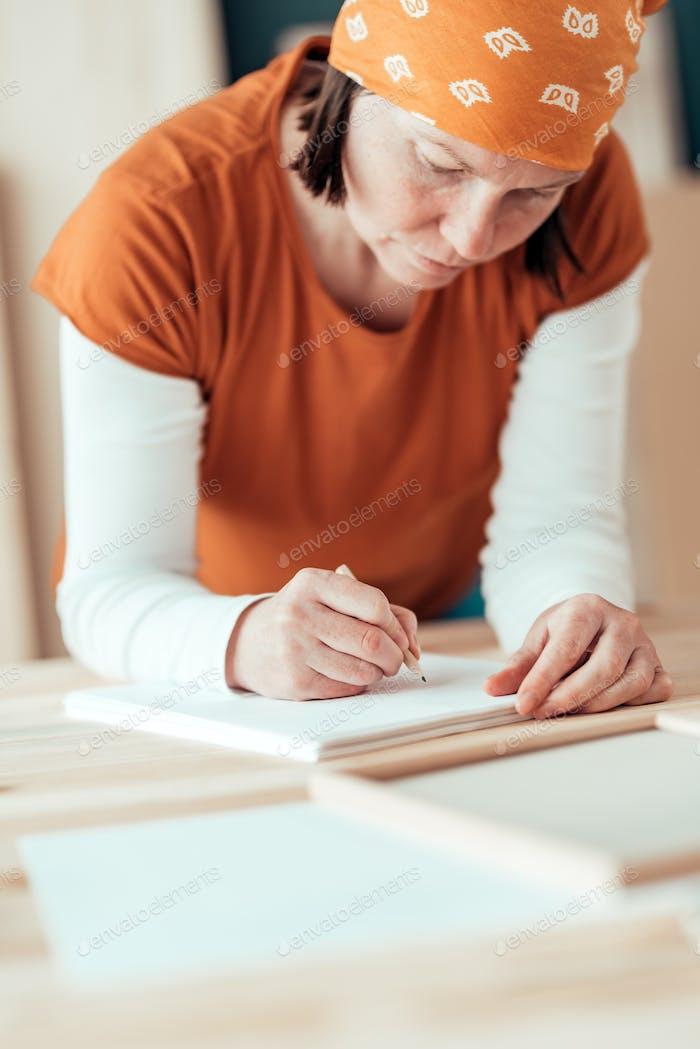 Weibliche Zimmermann Skizzieren Projekt Entwurf Notizen in Holzarbeiten