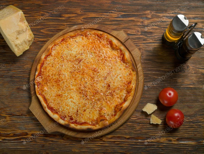 Pizza, tomatoes, cheese, olive oil on a wooden table
