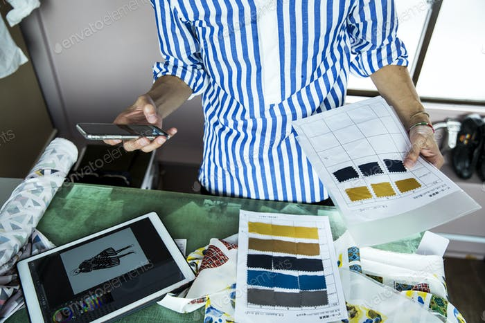 fashion designer working in his studio, looking at fabric samples, holding mobile phone.