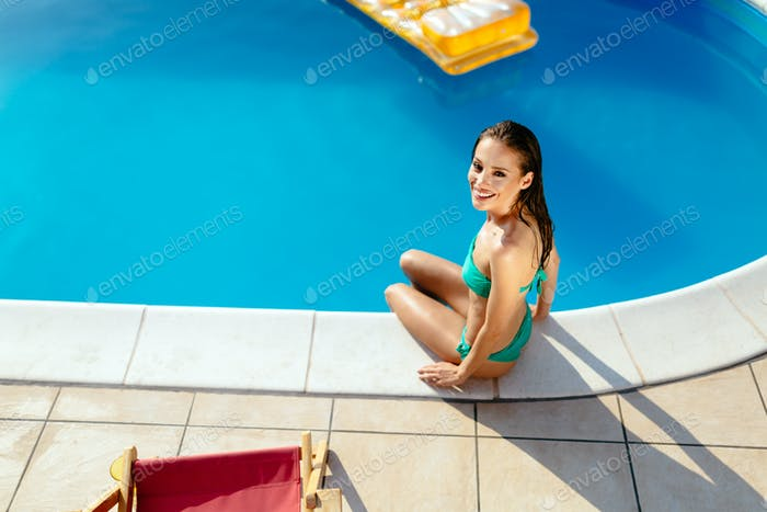 Beautiful woman enjoying vacation at poolside