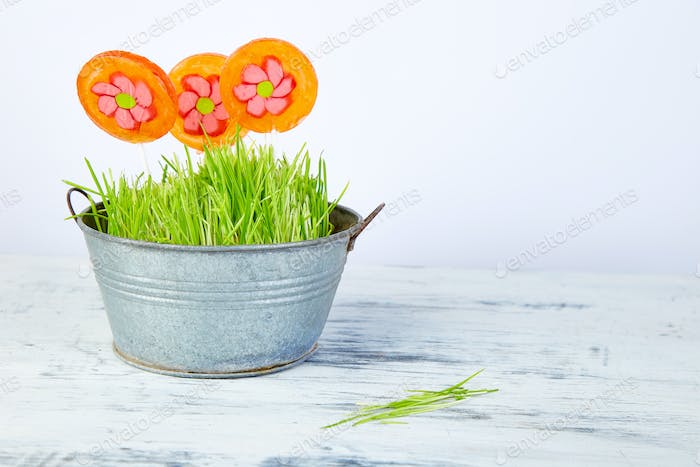 Spring concept. Candy lollipop flower in flowerpot with grass