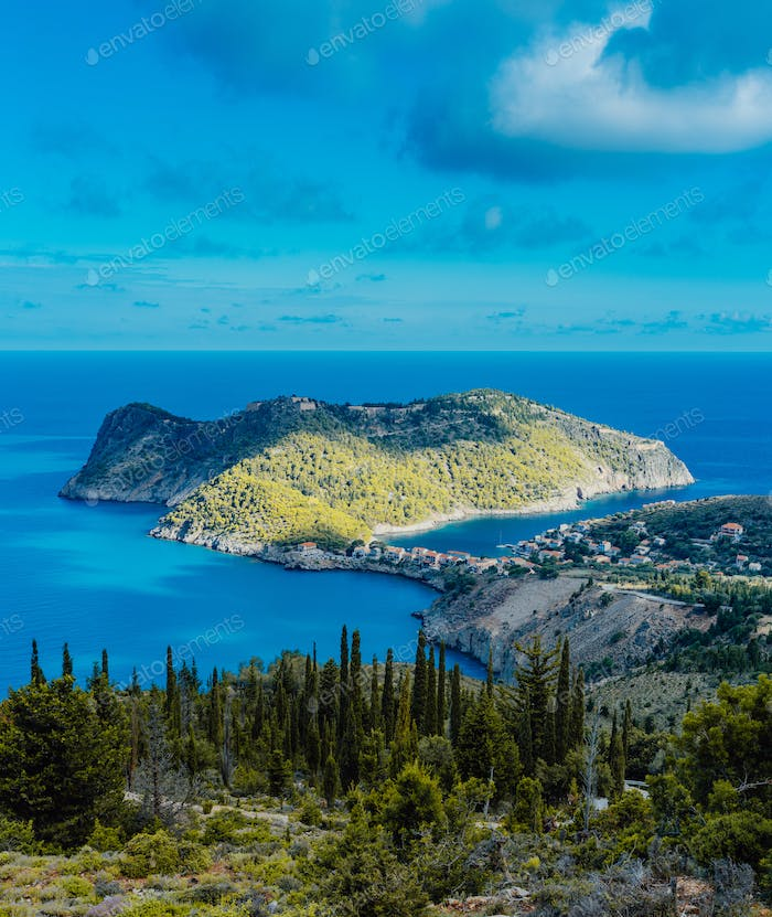 View to Assos village and beautiful blue sea. Cypress trees in foreground. Kefalonia island, Greece