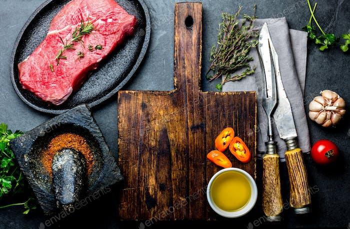 Frisches rohes Fleisch Steak Rinderfilet, Kräuter und Gewürze rund um Schneidebrett