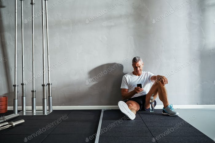 Mature man checking his messages after a health club workout