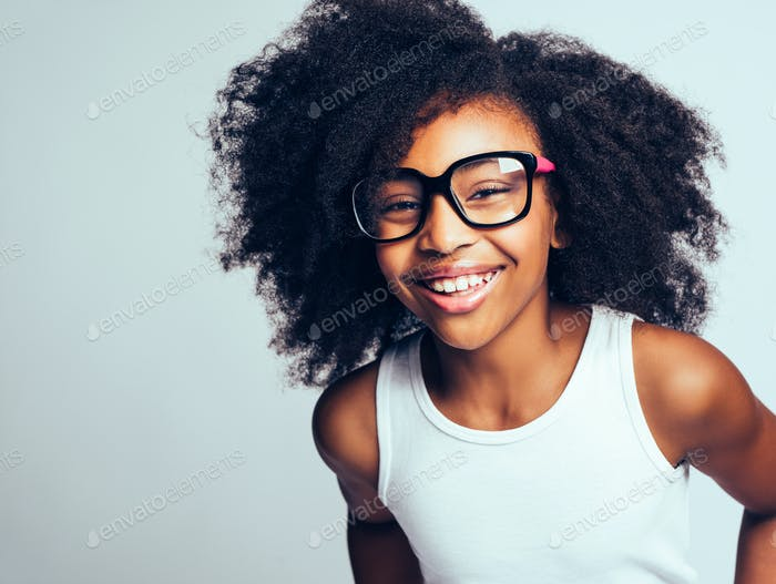 Laughing young African girl wearing glasses against a gray background