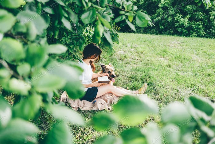 girl reads book sitting on blanket near large old dog on lawn green grass