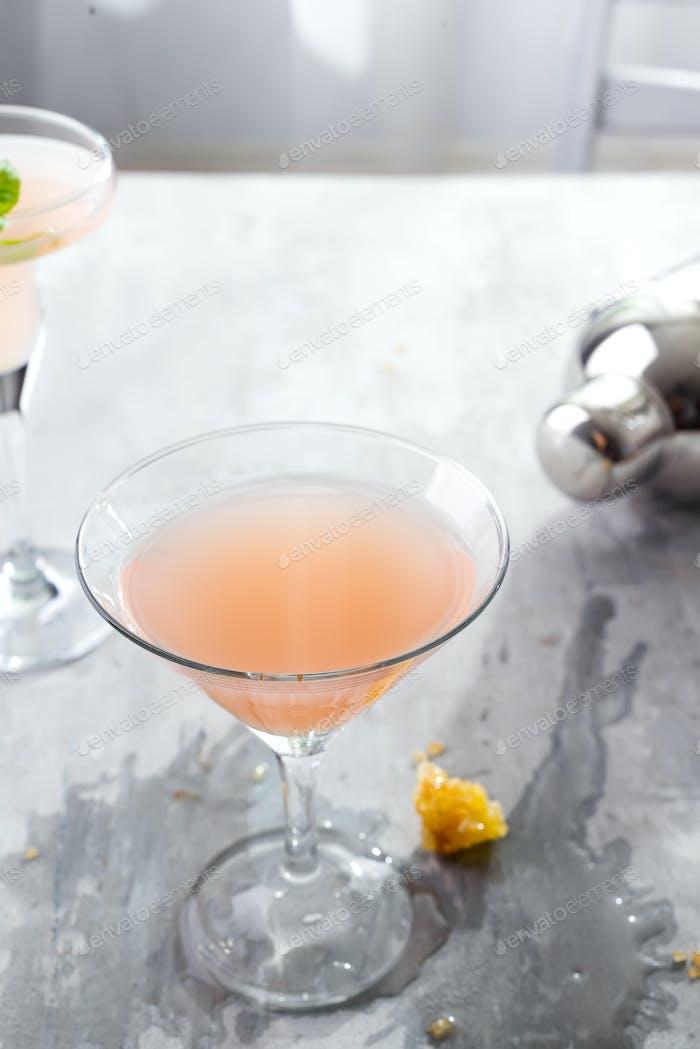 Bellini Cocktail mit Pfirsich und Honig, mit einem verschütteten Getränk auf einem Betonuntergrund