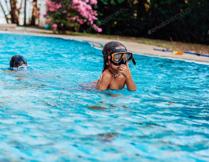 Two little kids diving into the water in swimming pool on their vacations