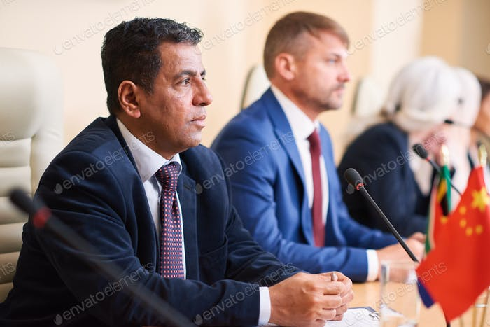 Mature serious politician listening to one of colleagues