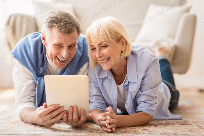 Excited mature couple browsing social media on tablet