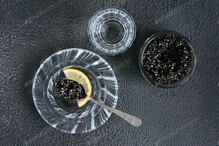 Black fish caviar on a black background.