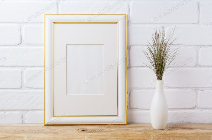 Gold decorated frame mockup with dark grass in elegant vase